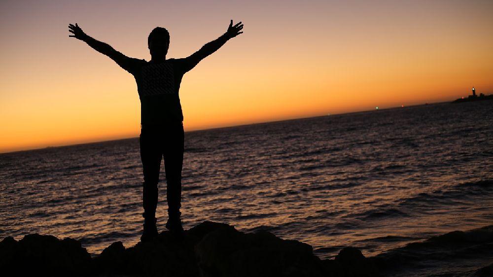 海の前の岩の上で夕日に向かって両手を広げる男性のシルエット