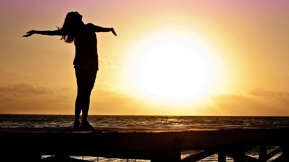 ビーチで夕日に向かって両手を広げて立つ女性のシルエット