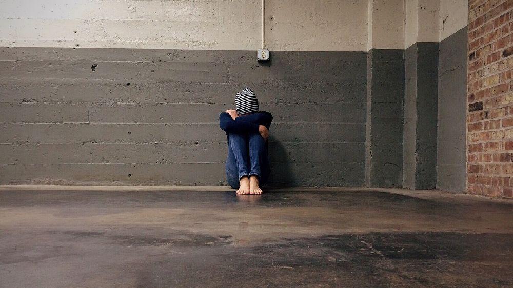部屋の片隅で膝を抱えて俯くニット帽を被った女性