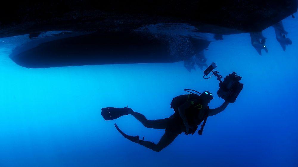 海の中に潜って張り込みをするカメラを持った探偵