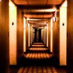 ホテル内の薄暗い通路。左右に各部屋が並んでいます。