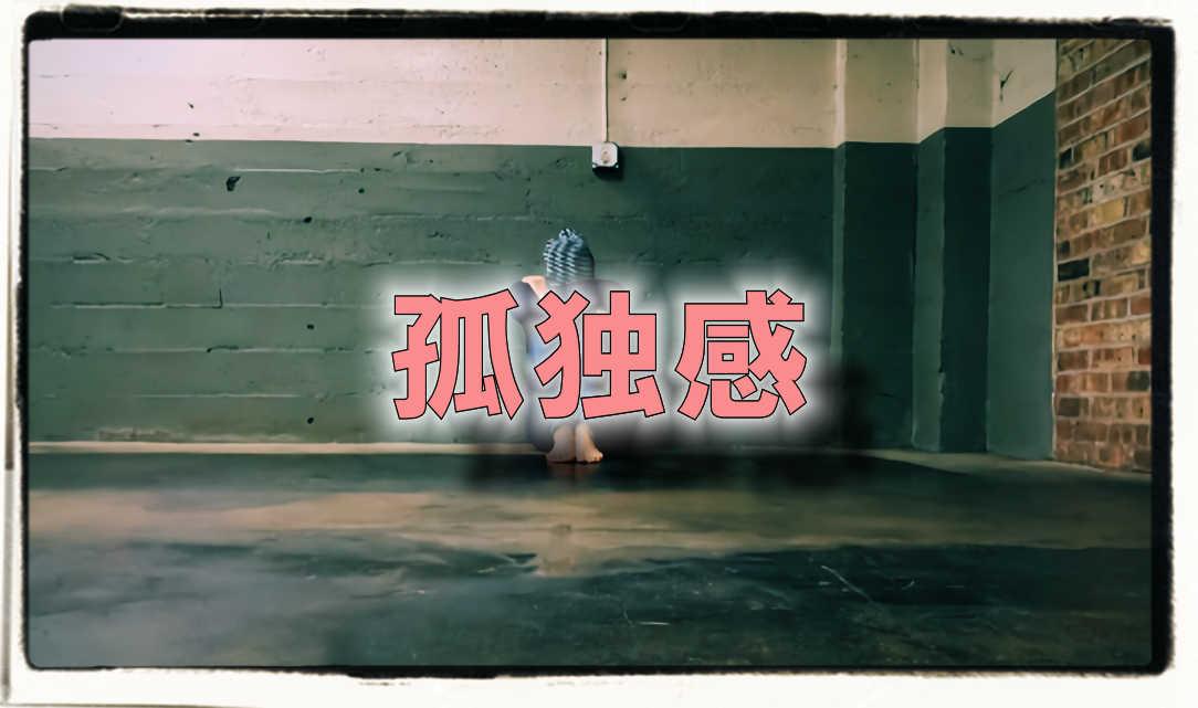 部屋に一人膝を抱えて蹲る女性の写真にピンクの文字で「孤独感」と書かれた画像です。
