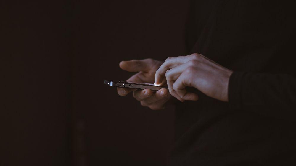 黒のiphoneを操作する黒セーターの探偵の手元