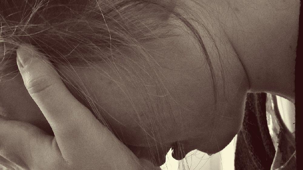 俯き右手を目に当てて泣く女性の顔アップモノクロ画像
