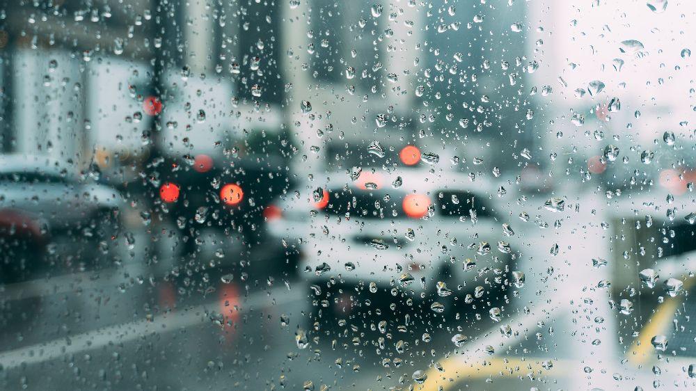 探偵車両内の窓越しに見た雨の道路