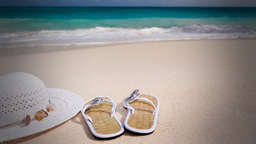 夏のビーチに置かれた白い麦わら帽子とサンダル