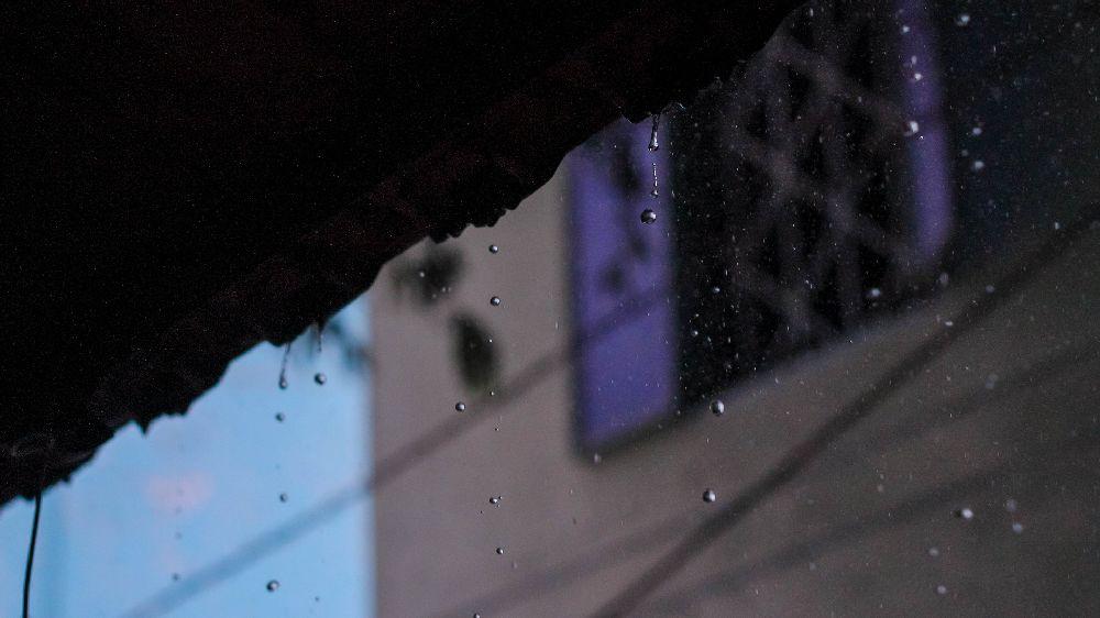 雨の中、車内で張り込み中の探偵から見た対象者宅の窓