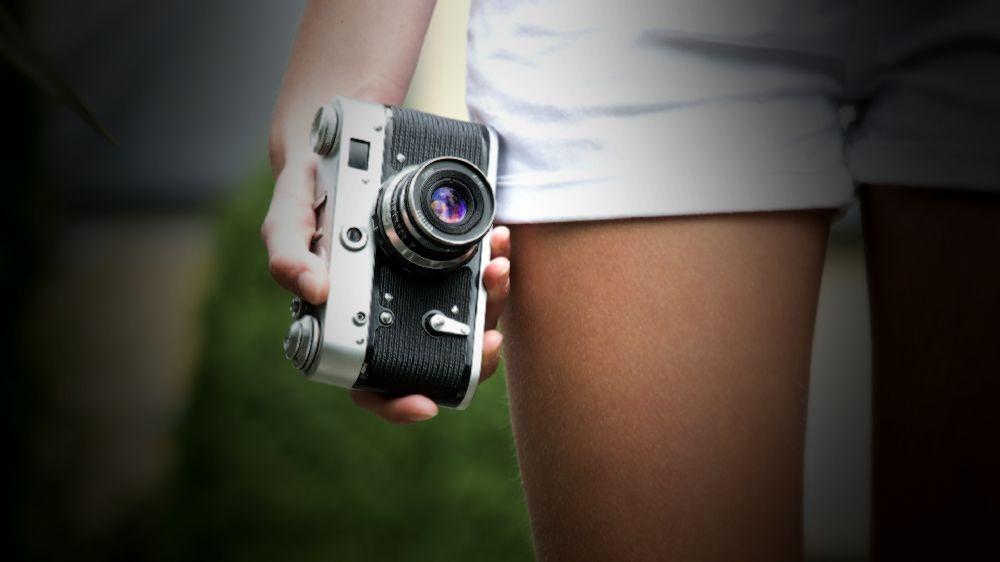 白いショートパンツを履いた女性の右手に一眼レフカメラ