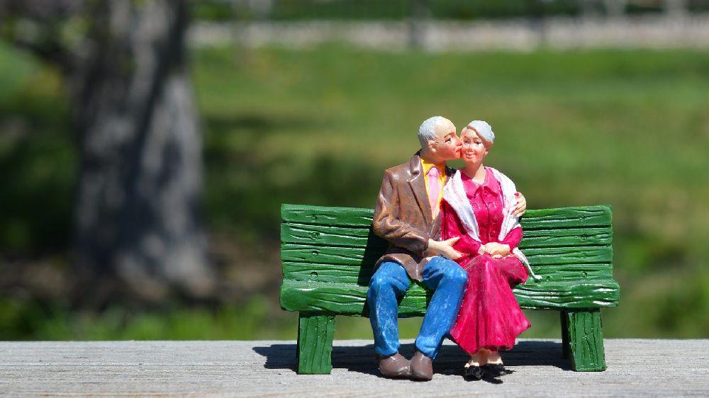 仲の良い夫婦人形がベンチに座ってキスをする