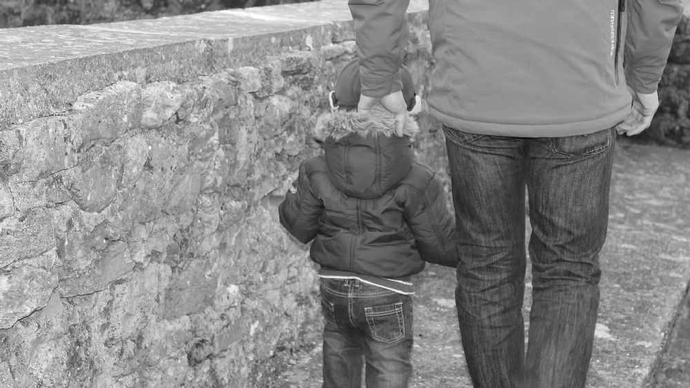 父親と幼い息子が歩くモノクロシルエット