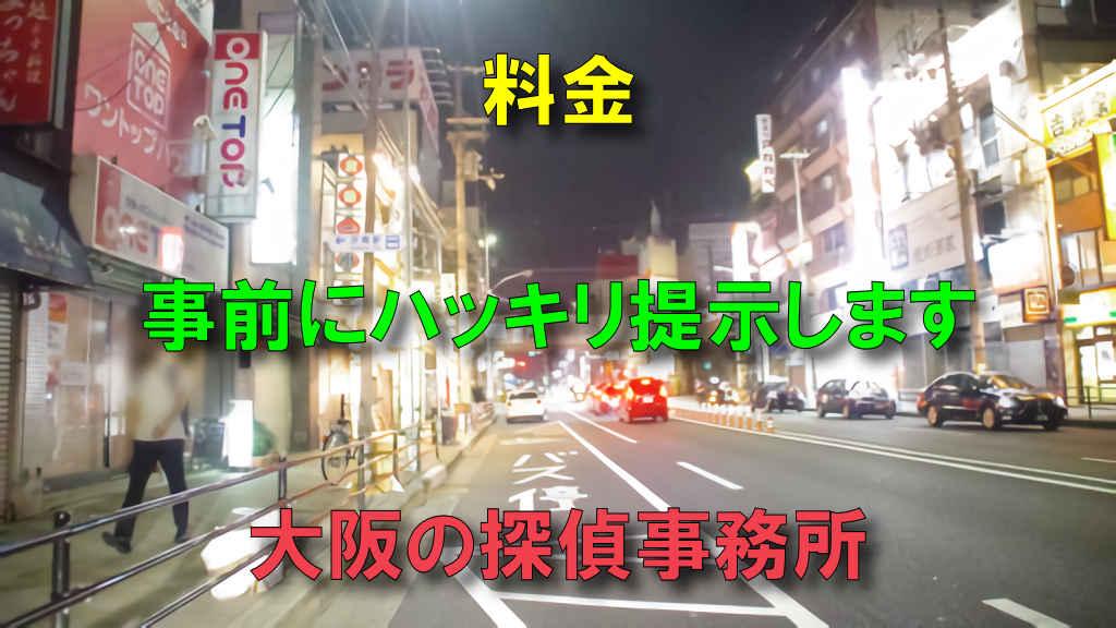 大阪の京橋にある国道1号線の路上の写真に「料金を事前にハッキリ提示します」と「大阪の探偵事務所」と文字が書かれている画像です。