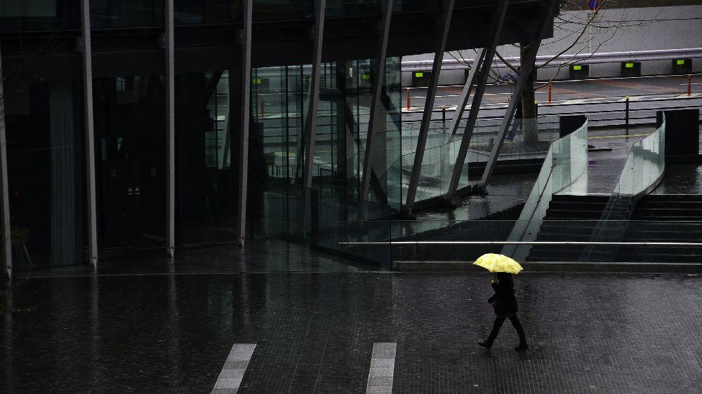 大阪市内のオフィス街を歩く彼の素行調査。スーツの彼が雨が降っており、黄色い傘を差している。