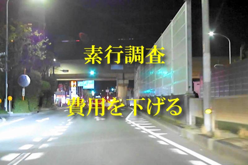 一般道を走る夜間のドライブレコーダーのキャプチャに黄色の文字で「素行調査の費用を下げる」と書かれている画像