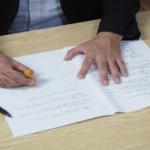不倫相手が示談書にサインし終え、押印する様子の画像です。