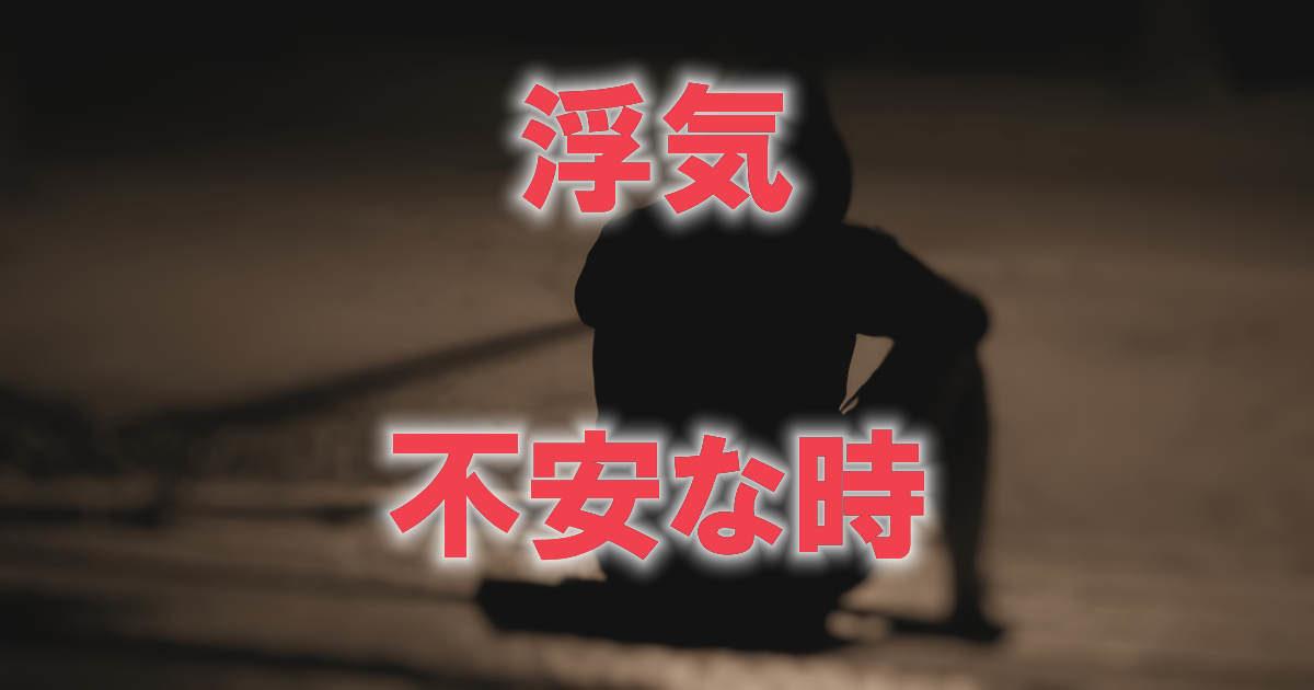 地面に座り込んだパーカーを被った男性の後ろ姿に「浮気」「不安な時」と赤字で書かれた画像です。