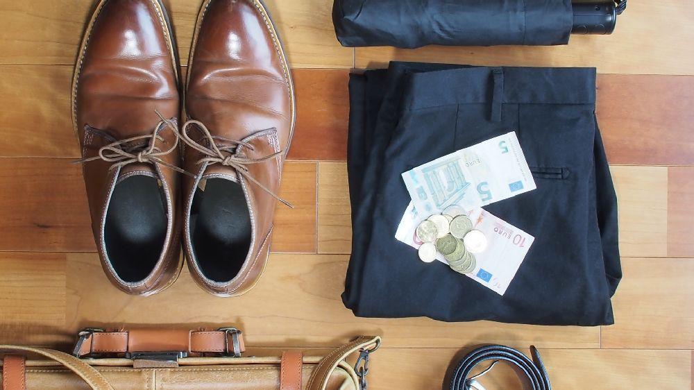 単身赴任へ出掛ける夫の荷物(茶色の革靴、黒スーツ、茶色のビジネスバッグ、折り畳み傘など)