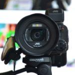 三脚に設置された黒いビデオカメラ