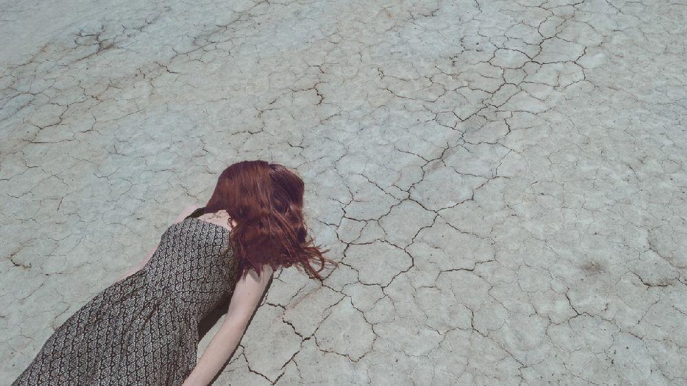悩んで落ち込み大地に横たわる脱力した女性
