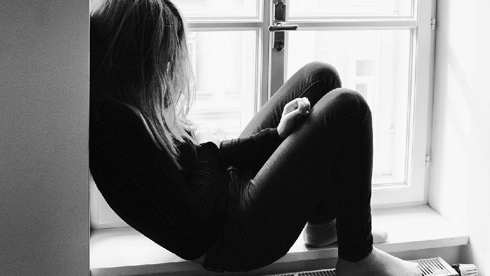 浮気をされて窓際にもたれ落ち込む女性