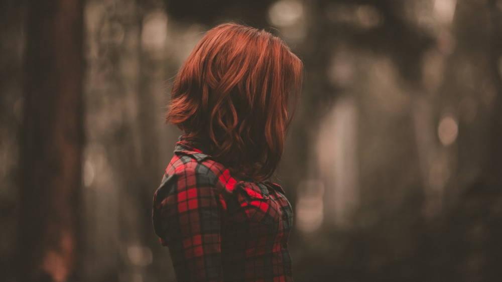 雨の森の中で落ち込む女性