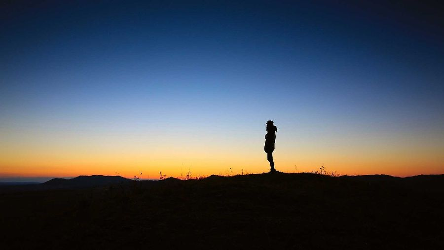 夕焼け空の荒野に佇む孤独な男性のシルエット