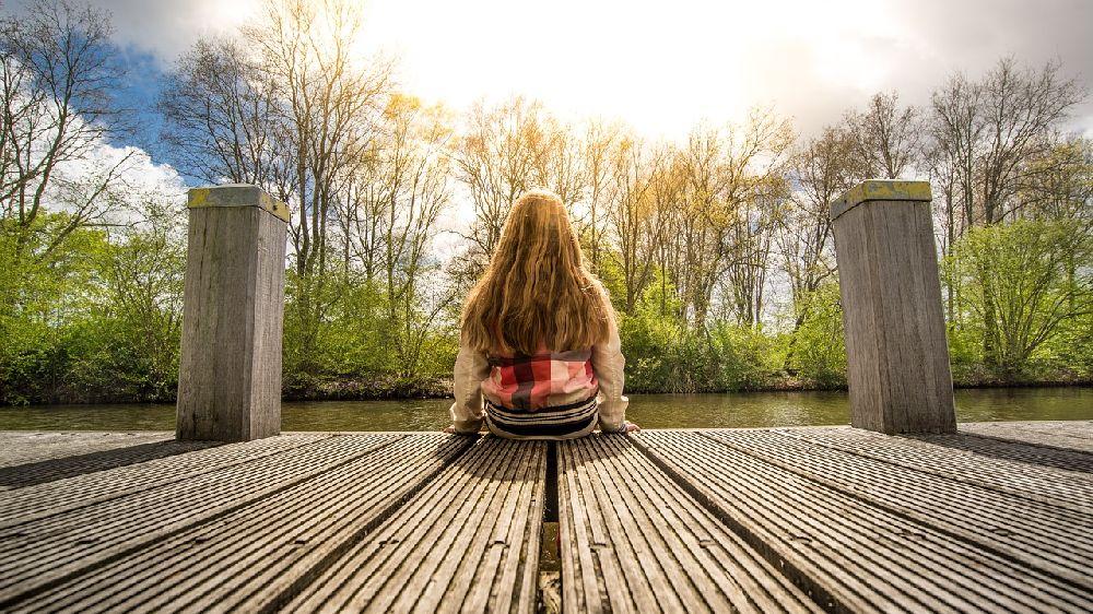 橋に座って考える女性の後姿