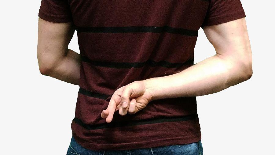嘘を付く男性の後ろ姿。 背後で指を交差させている。