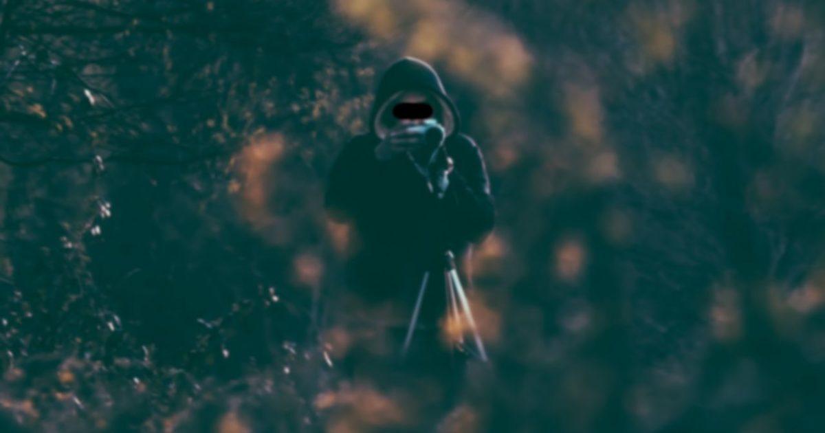 茂みに隠れて証拠写真を撮る探偵。パーカーを被っています。