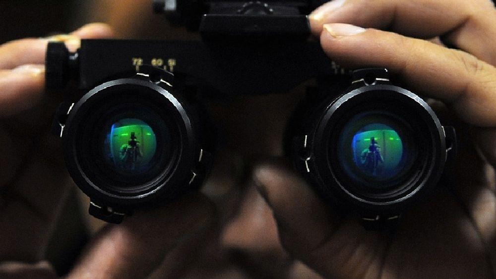 ナイトビジョン(暗視カメラ)を構える探偵の顔アップ