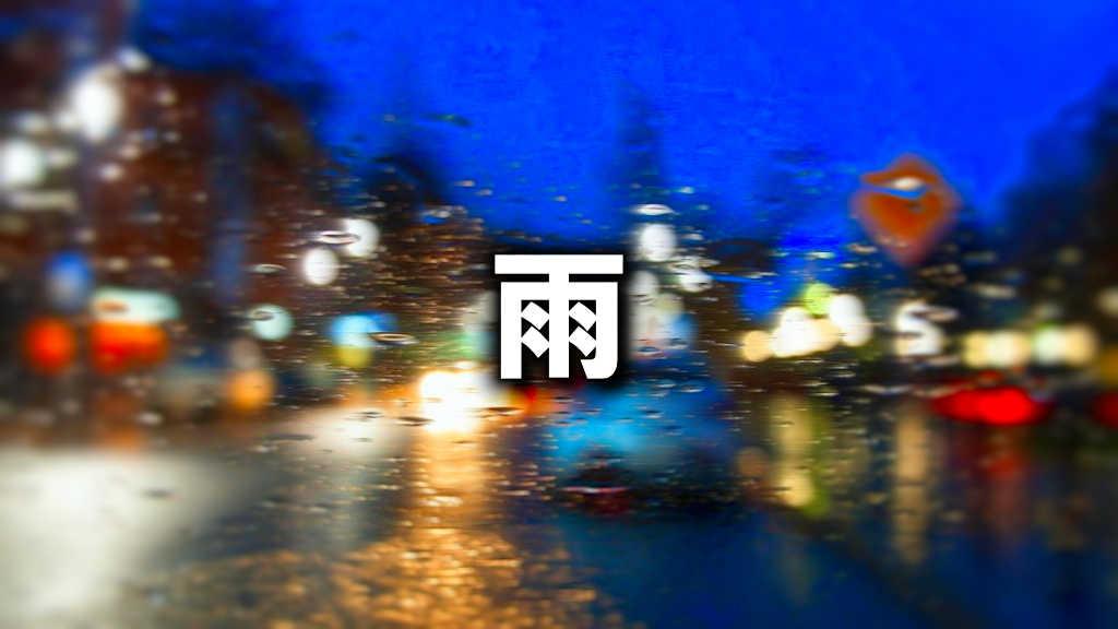 雨が降って車の窓ガラスが濡れて滲んでいる夕暮れの街の写真です。
