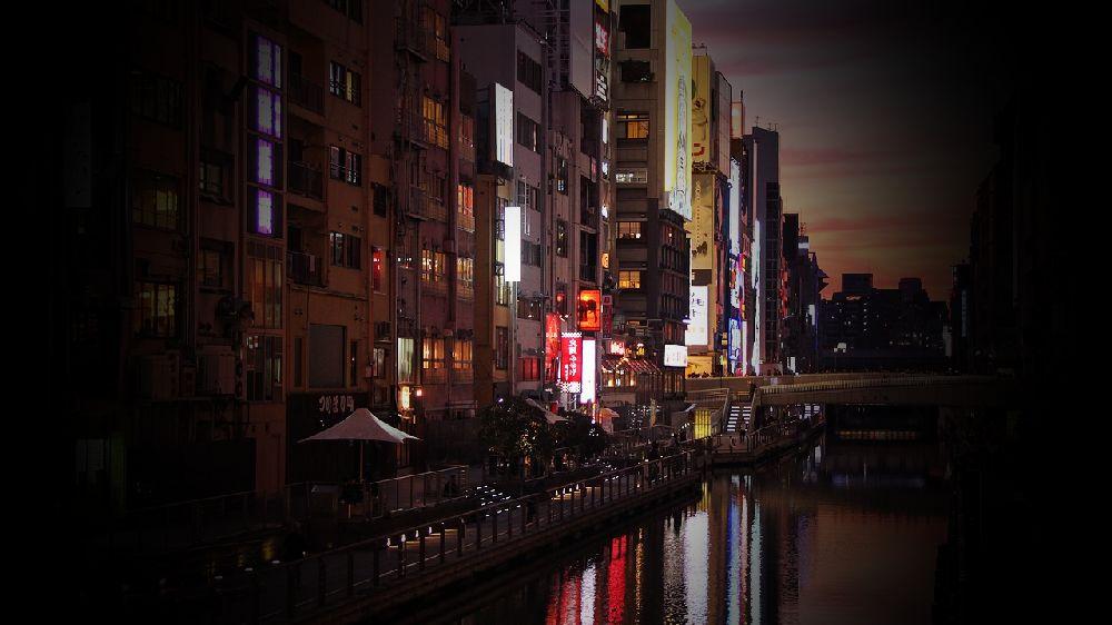 大阪の夜の道頓堀付近。橋の上からの川と店舗。