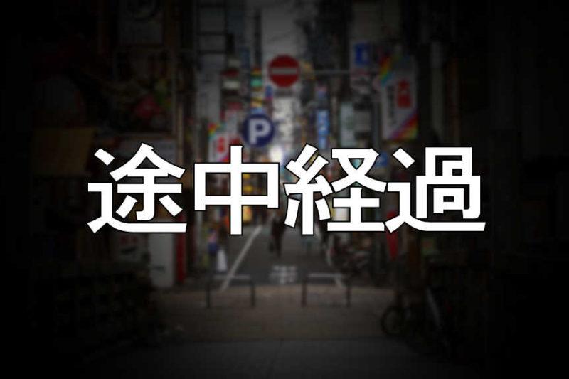 中央に「途中経過」と書かれた大阪の街の写真です。街の景色はぼかしを掛けています。