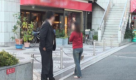 本人と同女性が同珈琲ショップ前にて笑顔で会話中をしています。初対面ではなさそうです。