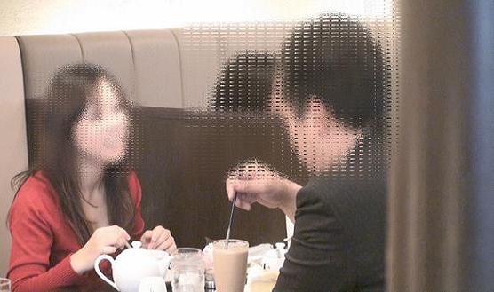 同珈琲ショップ内のテーブル席で向かい合って飲食をする本人と同女性の様子です。笑顔で親しげに会話をしています。