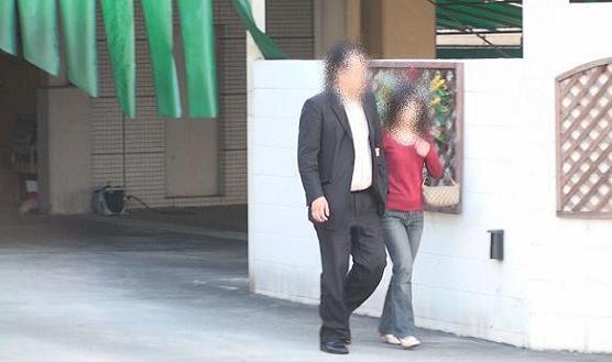 ②同ホテル南側正面出入り口より腕を組みながら徒歩にて出る本人と同女性。本人は堂々と、同女性はやや顔を伏せています。