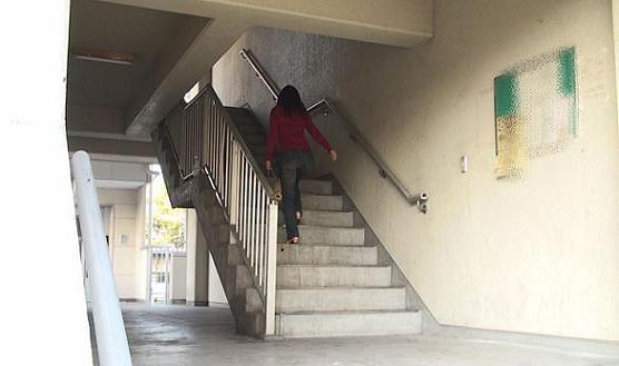 やや古い感じの同マンション1号棟東側の階段を1階から2階へ向かって上がる同女性の後姿です。