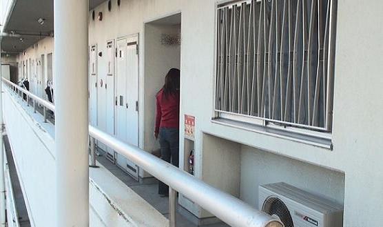 同マンション1号棟○○○号室玄関前に立ち、玄関ドアを開錠する様子の同女性の後姿です。