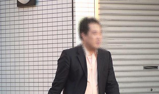 徒歩で勤務先より出る黒スーツを着た本人の上半身アップ画像です。モザイクが掛かっていて表情がわかりませんが、実際はノホホンとした表情です。
