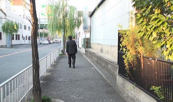 黒スーツを着た本人が徒歩にて東へ向かう後姿です。ダラダラとゆっくり歩いています。
