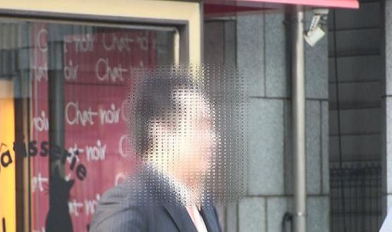 同珈琲ショップ前にて人を待つ本人の顔アップ画像です。モザイクが掛かっていますが、シャキッとした表情です。